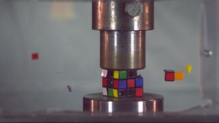 SUPER SLOW MOTION: rubik's cube and hockey puck with hydraulic press